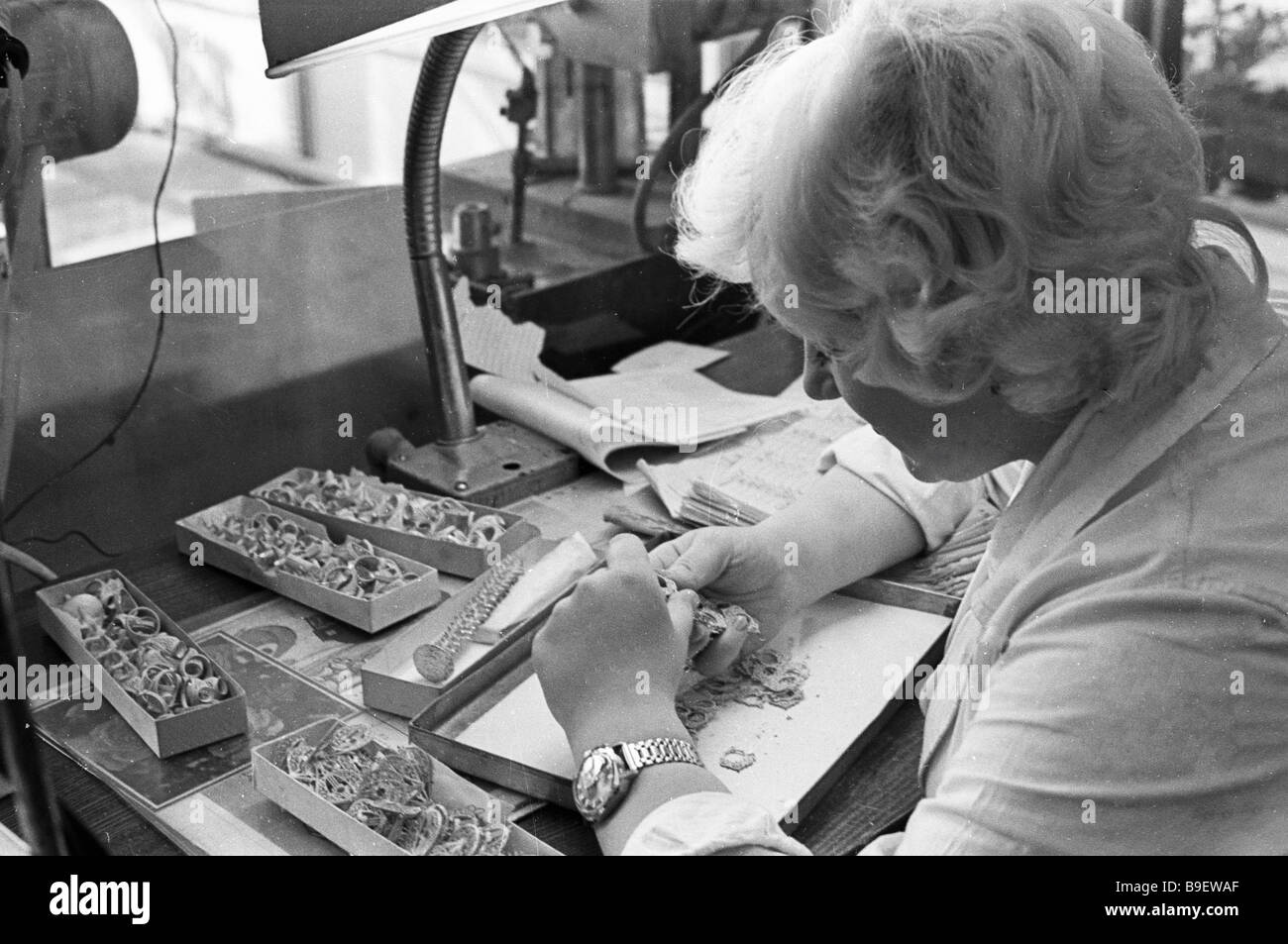 A Urals jewel factory quality controller is checking earrings - Stock Image