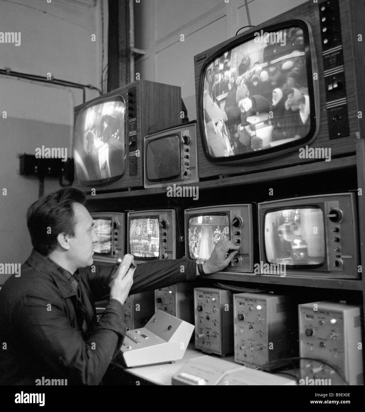 A dispatcher is receiving footage from the cameras fixed in the salesrooms of the shop to study the consumer demand - Stock Image