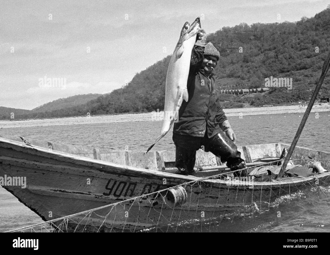 Fisherman Nikolai Romanov with his catch a 28 kg chinook salmon - Stock Image
