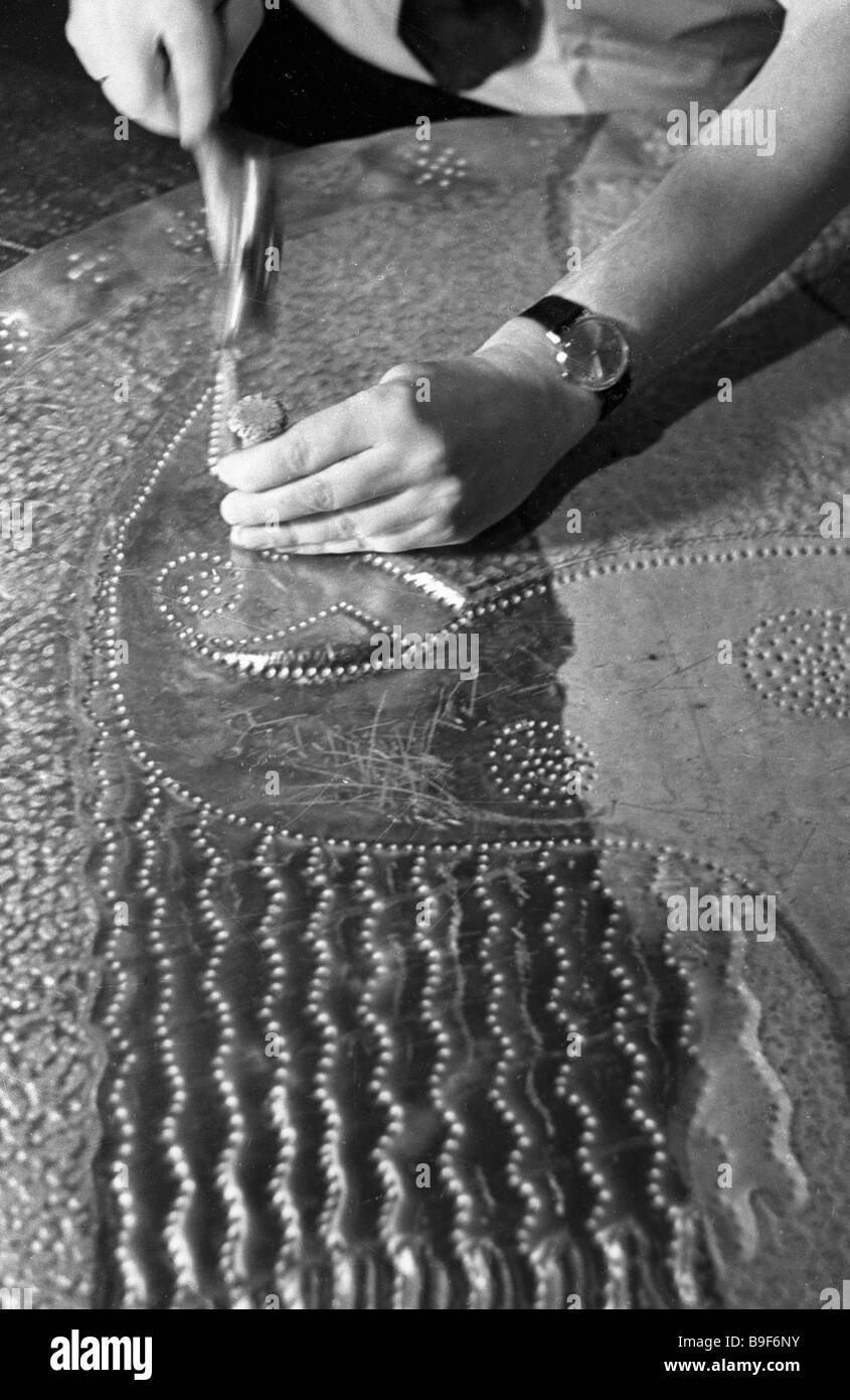 An artist working on an embossed relief - Stock Image