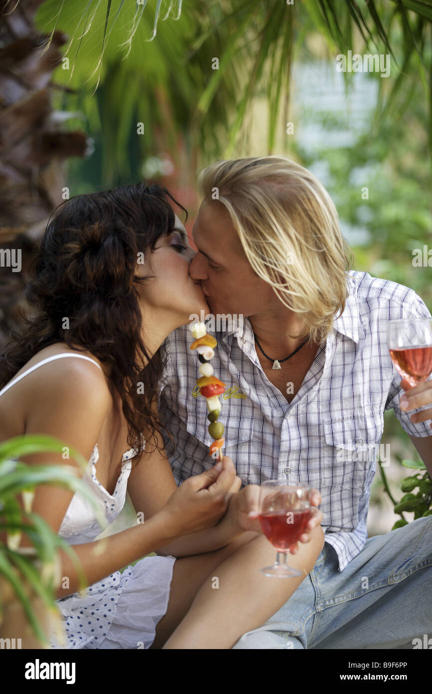 couple falling in love kiss beverage holding cheerfully detail series people love-pair leisurewear love affection - Stock Image