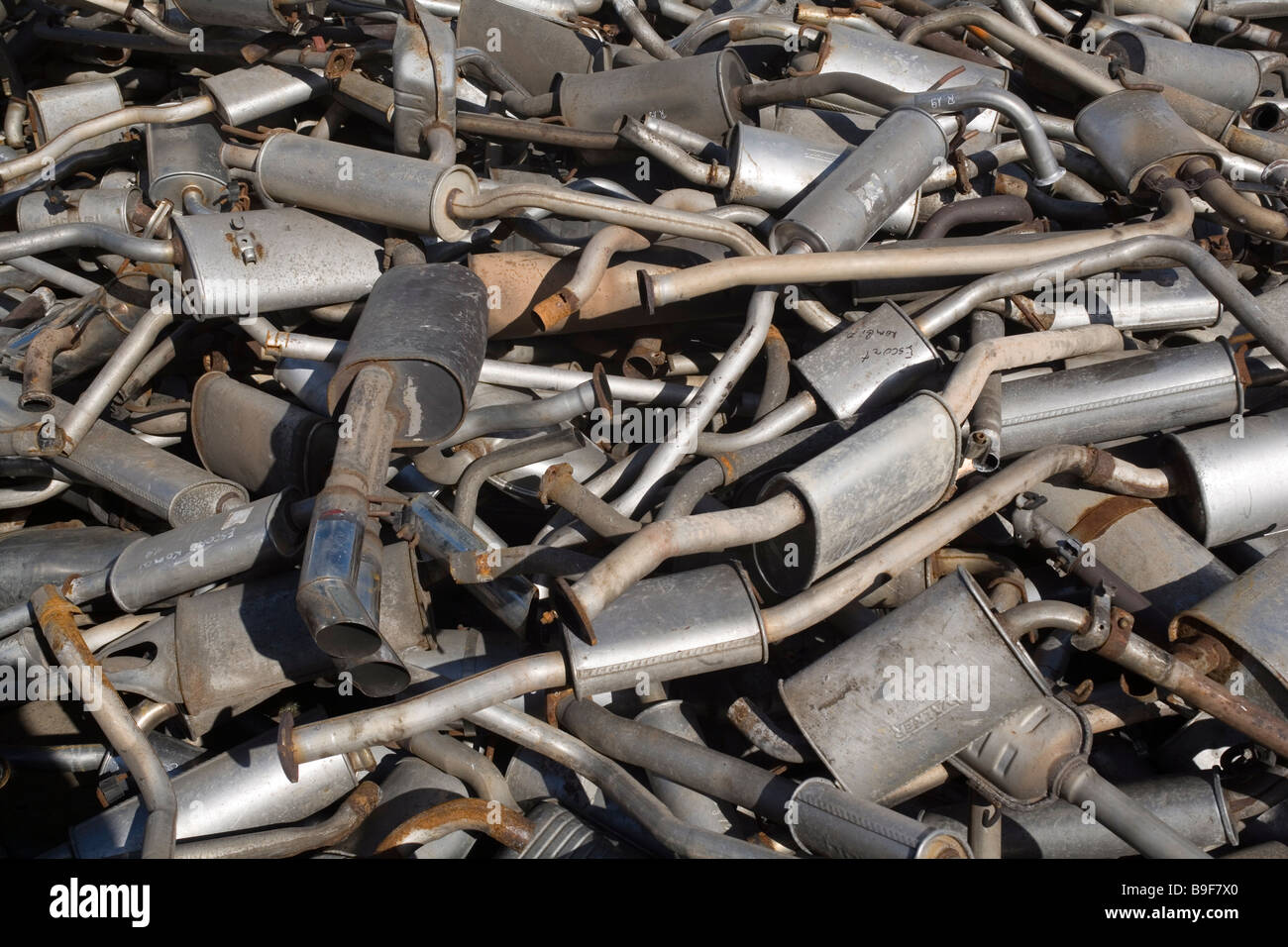 Old exhaust pipes on a scrap yard - Stock Image