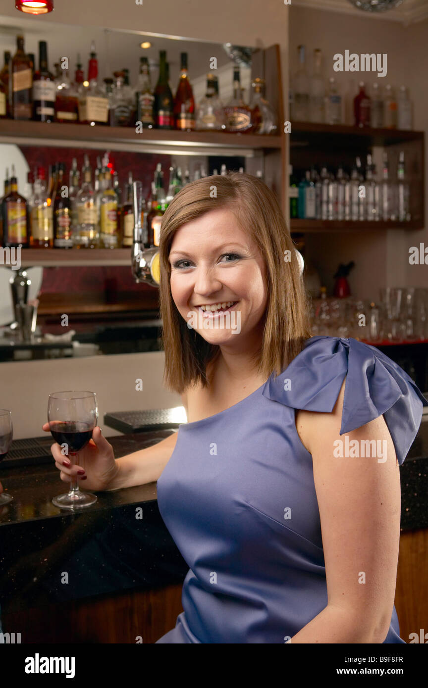 Young Woman having a drink at a bar - Stock Image