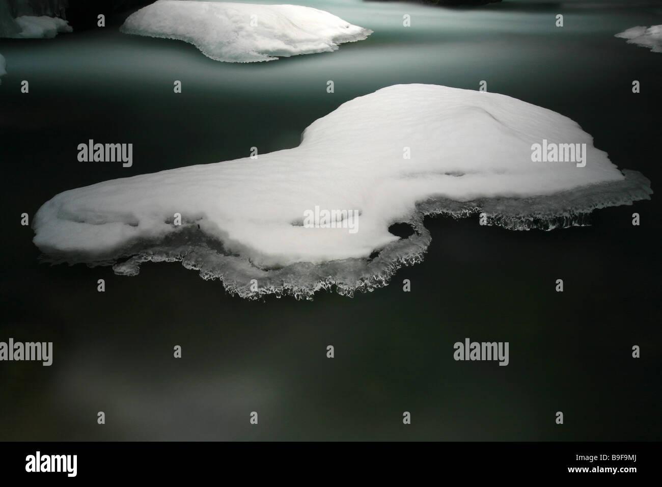 Snow and ice over rocks in Rauma river in Romsdalen valley, Rauma kommune, Møre og Romsdal, Norway. - Stock Image