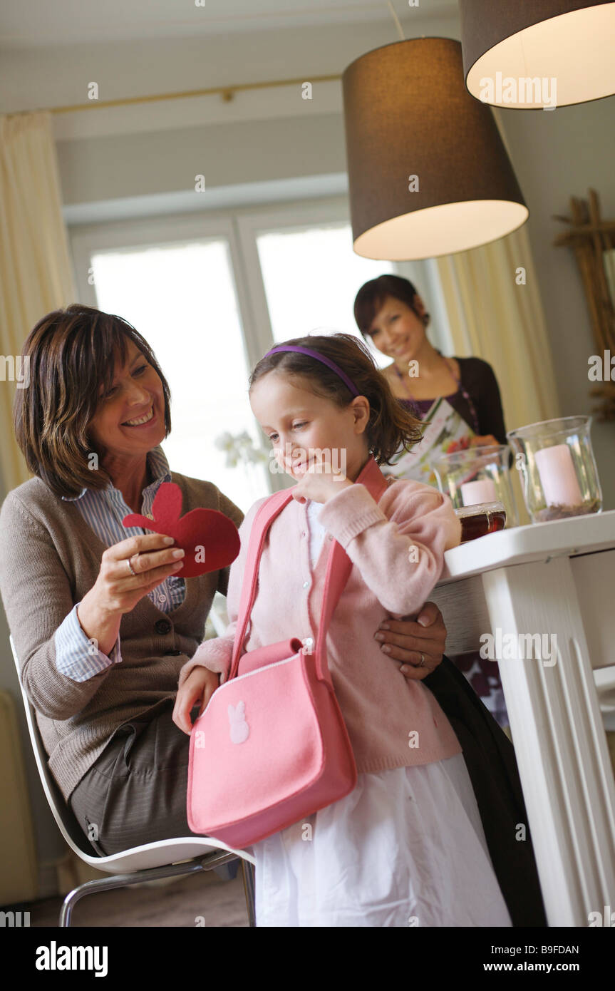 Woman giving present to her granddaughter at breakfast table - Stock Image