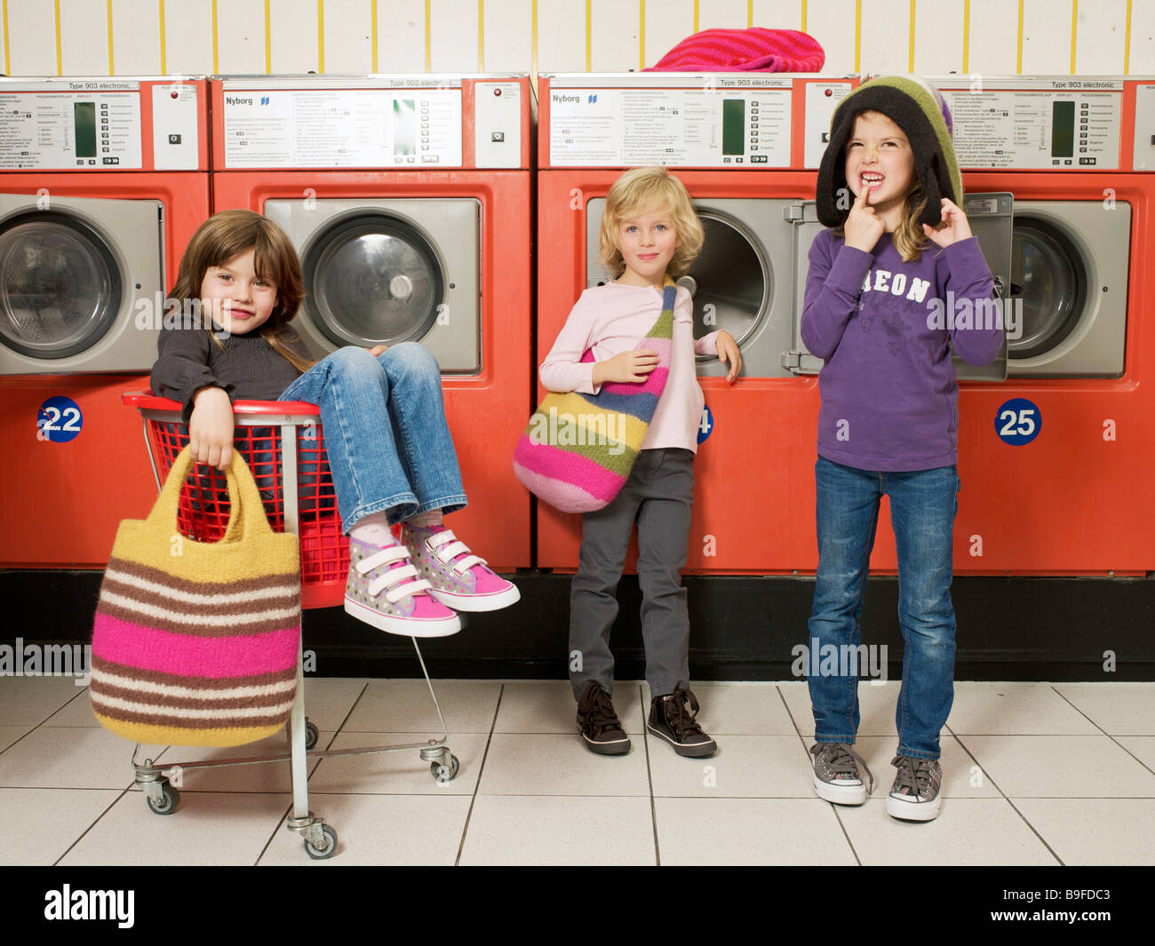 Three children in front of washing machines - Stock Image