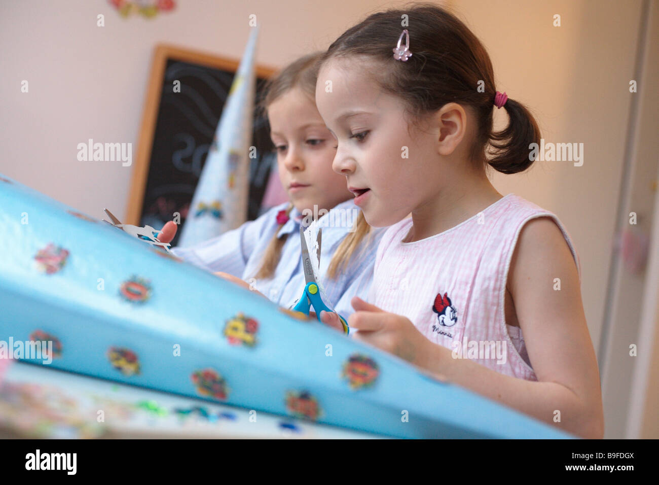 Side profile of two girls making cardboard cone - Stock Image