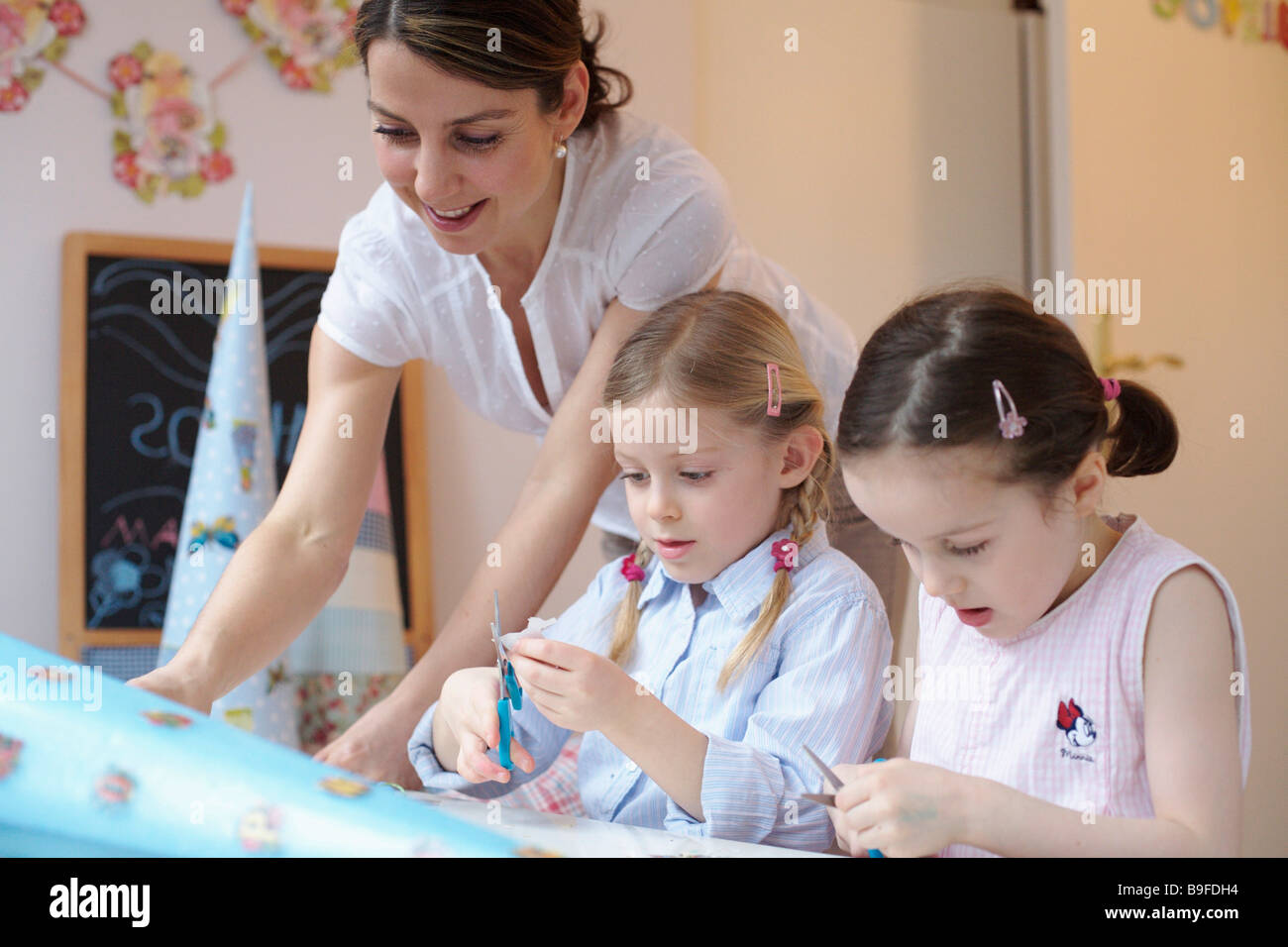 Woman helping her two daughters to decorate cardboard cone - Stock Image