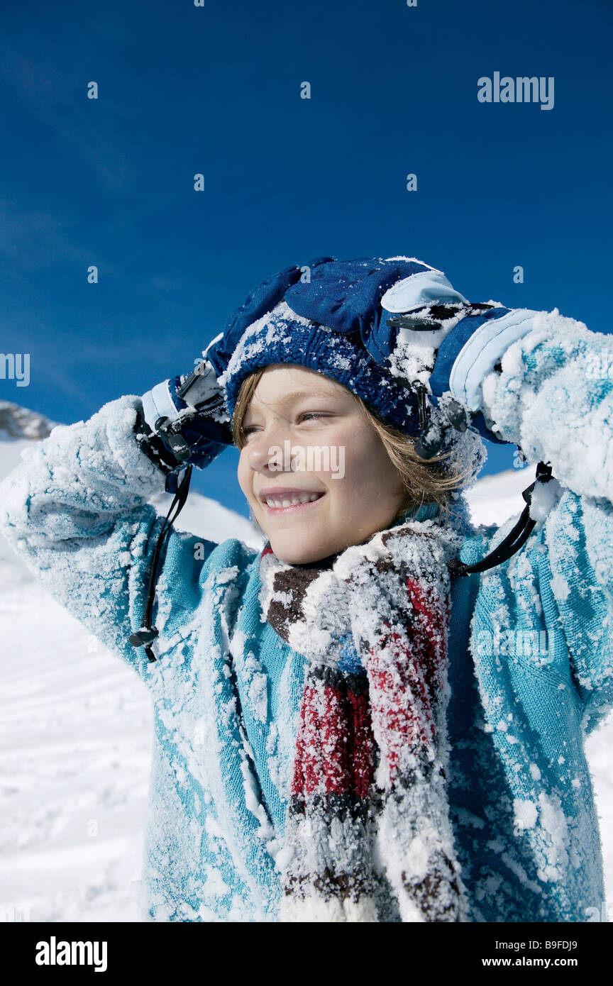 Portrait of boy smiling on snowcovered landscape - Stock Image