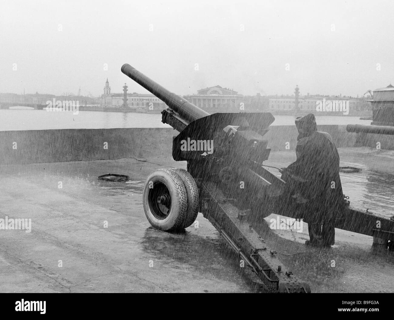 An artilleryman firing a cannon at noon on a bastion in the Peter and Paul Fortress - Stock Image
