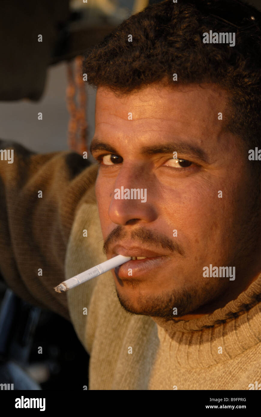 Egypt man cigarette smokes portrait broached Africa people native Egyptians smokers seriously self-confidence evening - Stock Image