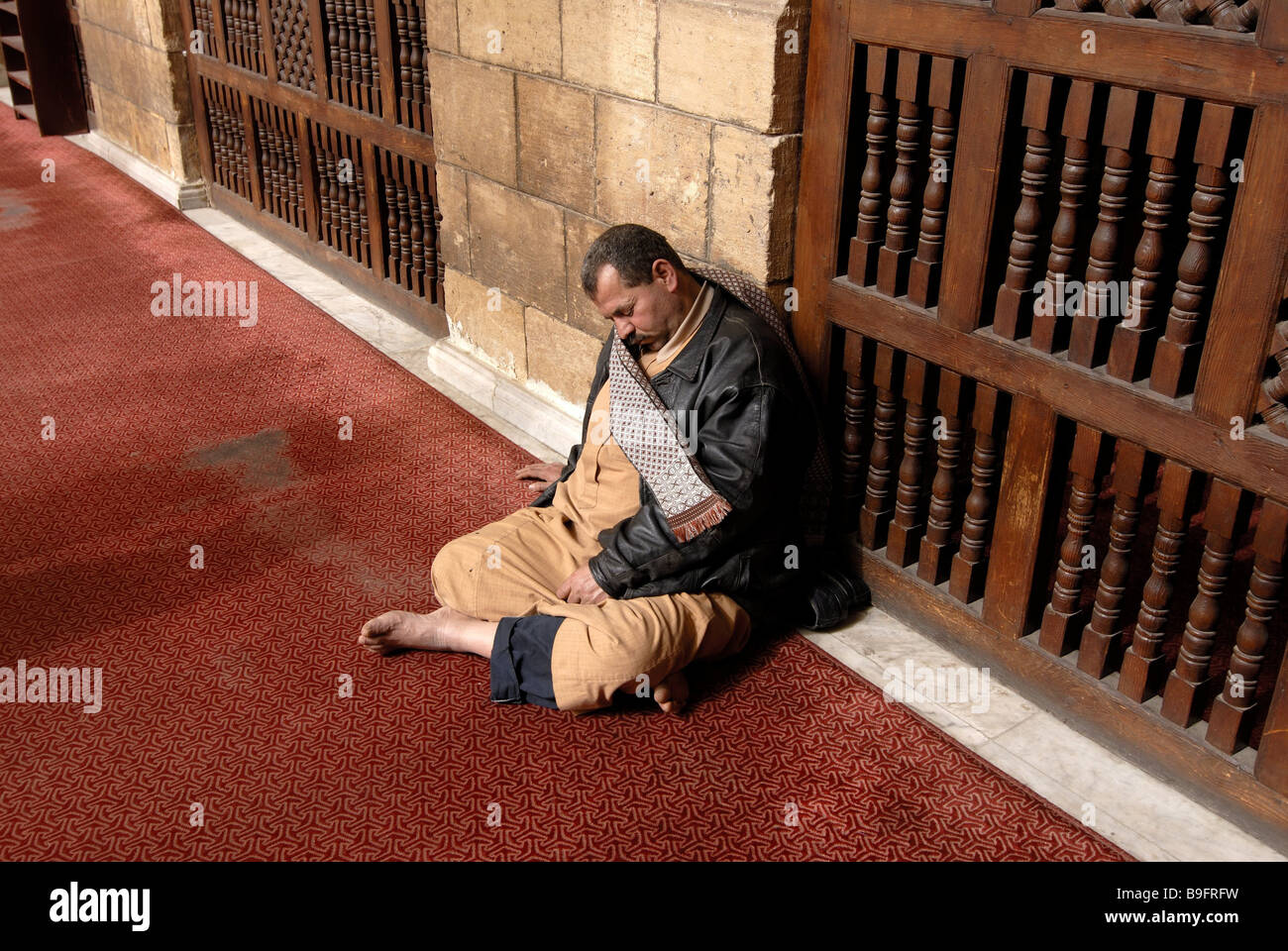 Sits Egypt Cairo Al Azhar mosque man sleeping people man Muslim creditors cross-legged resting tiredness exhaustion - Stock Image