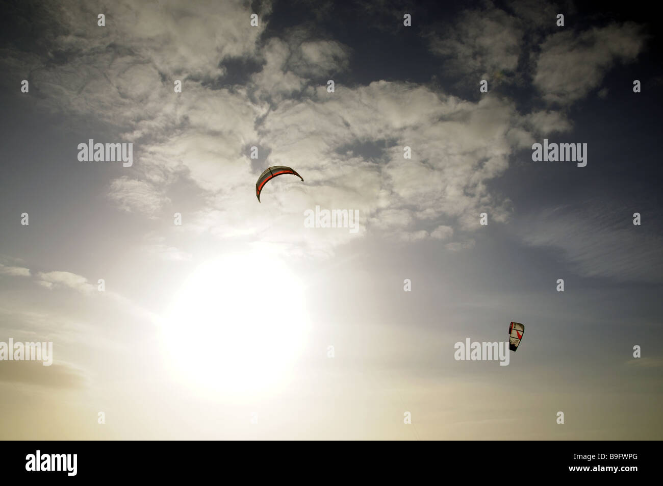 Pair of Power Kites Against Sun and Natural Sky - Stock Image