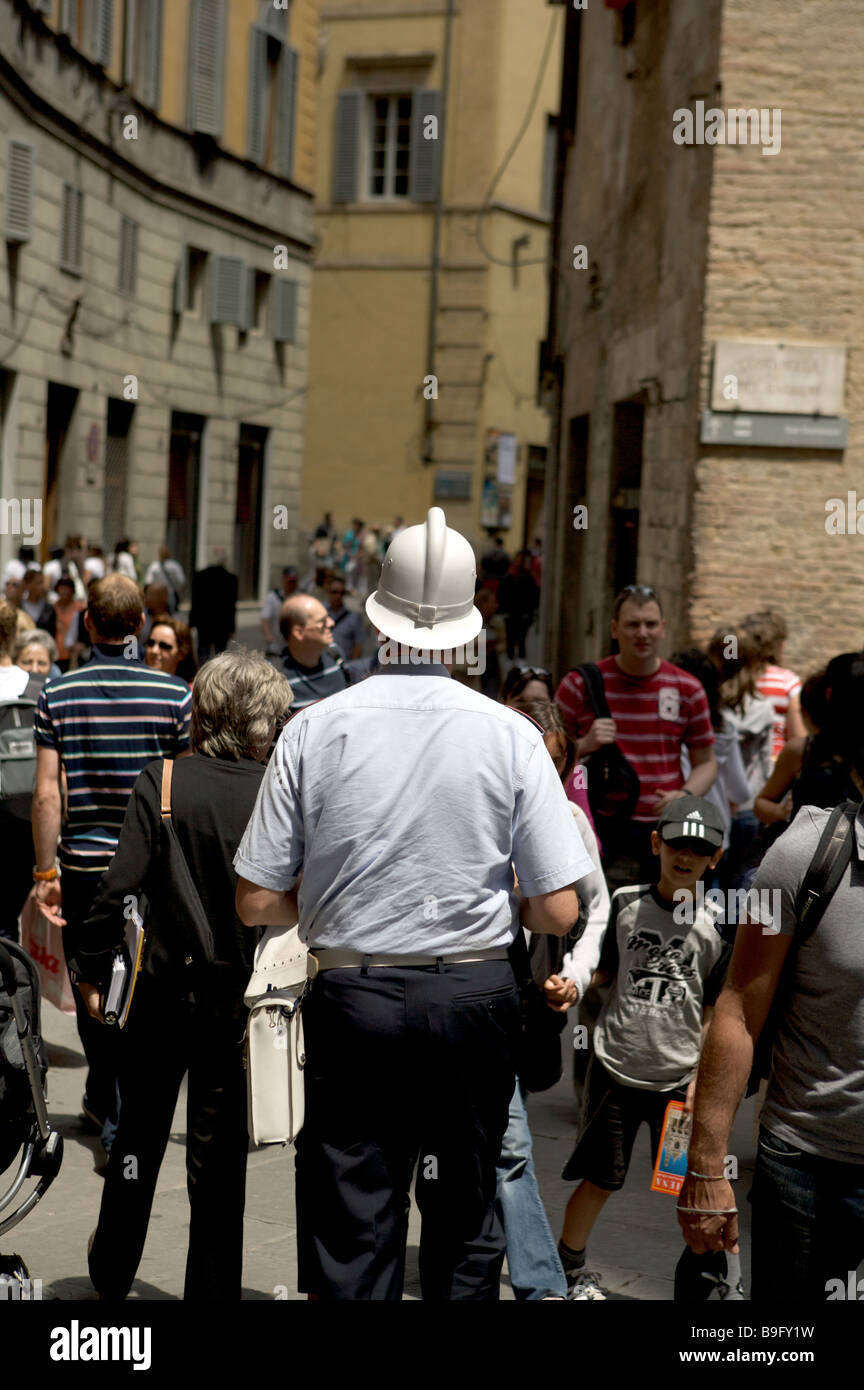 A carabiniere police officer walks down a busy street of tourists in Siena Italy. - Stock Image