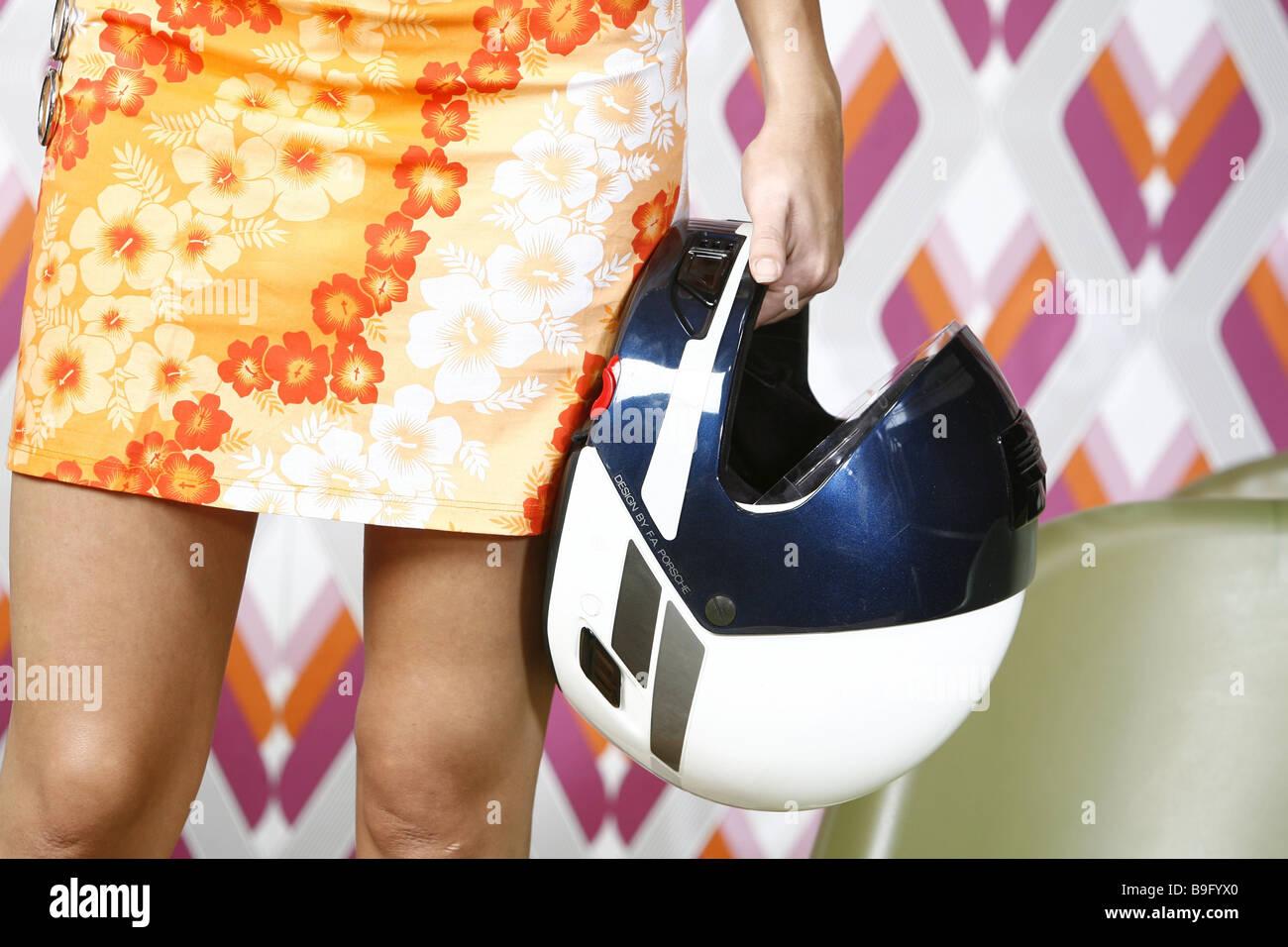 Woman stands miniskirt detail legs hand motorcycle-helmet holding Retro people dress summer-dress helmet carries - Stock Image