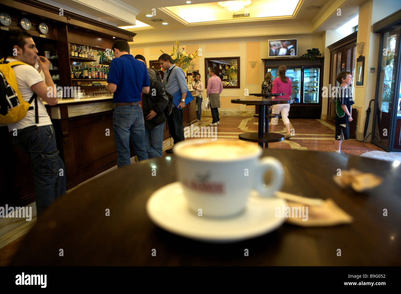 A coffee shop in Siena with a cup of coffee in the foreground and people in the background - Stock Image