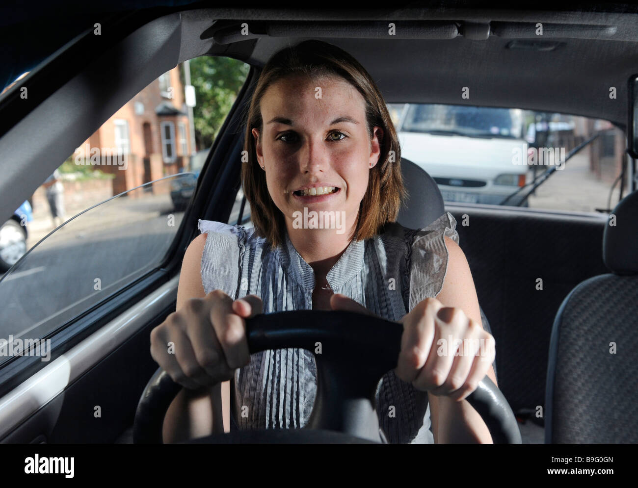 A nervous but determined female learner driver sits gripping the steering wheel of a car - Stock Image