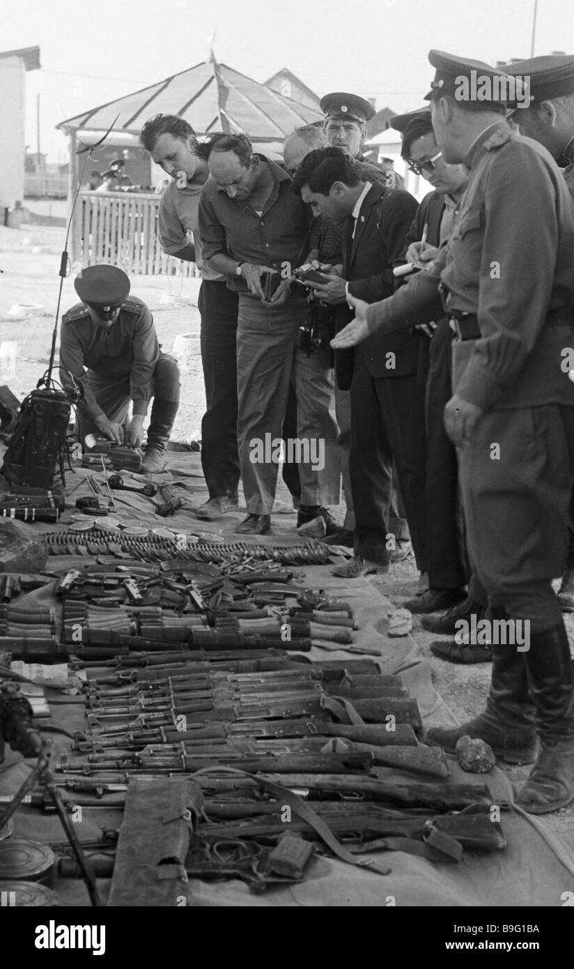 A border guard demonstrating journalists weapons gear and ammunition captured from Chinese trespassers - Stock Image