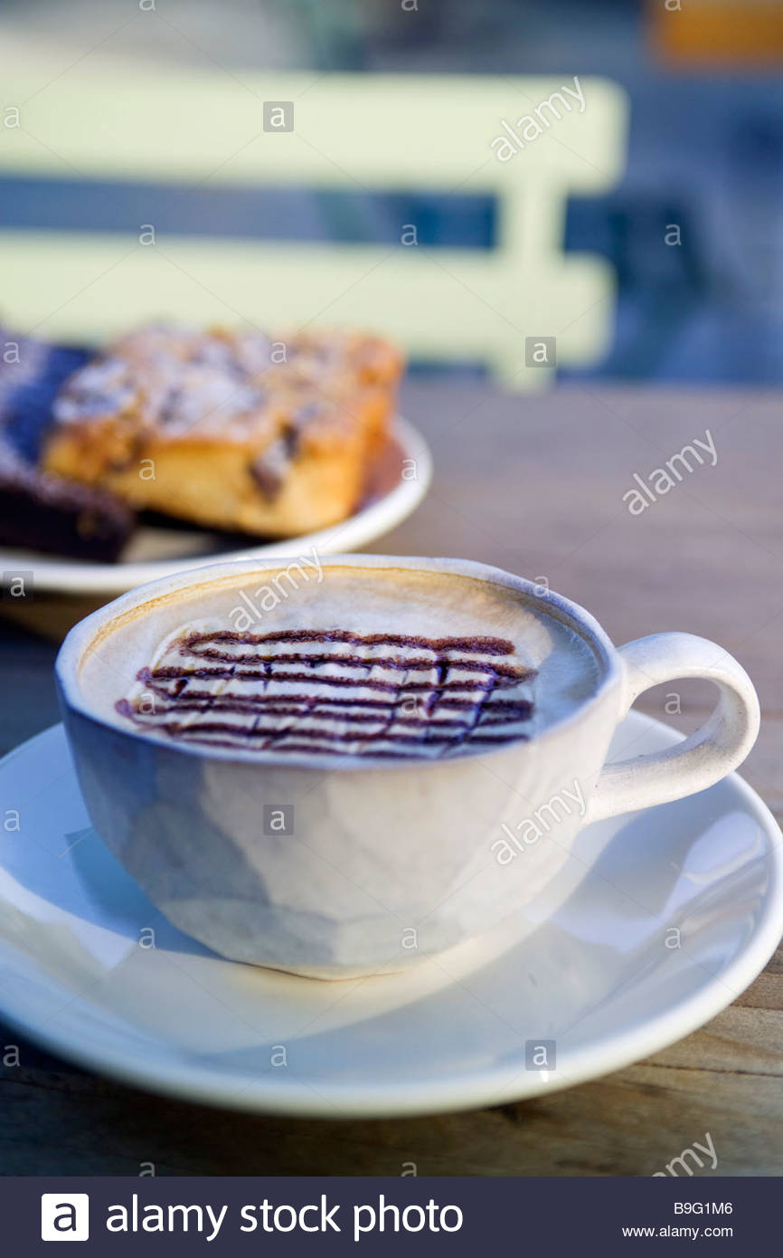 Cappuccino coffee with cakes on wooden table outdoors Terrain at Styer s 914 Baltimore Pike Glen Mills PA 19342 - Stock Image