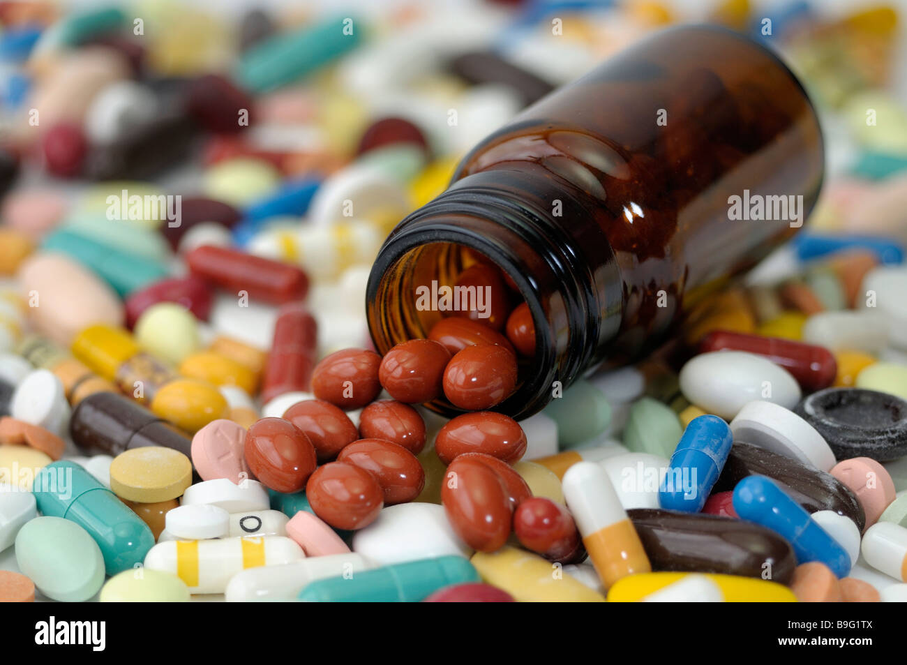 Colorful tablets with a small bottle studio picture - Stock Image