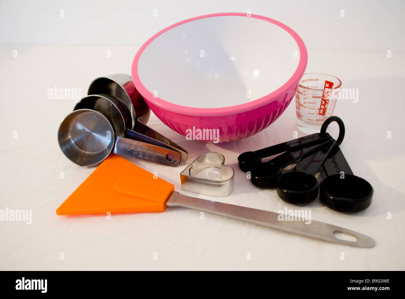Selection of weighing and measuring kitchen utensils inc. pink bowl, Pyrex jug & measuring spoons on a white - Stock Image