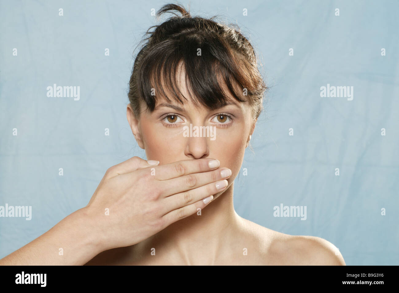 Woman young gesture hand mouth keeps closed portrait - Stock Image