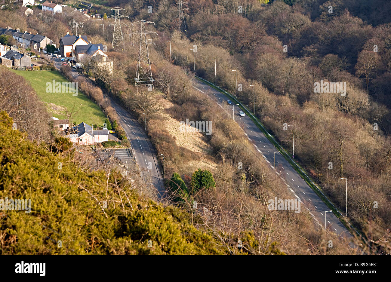 Houses and pylons near the three lane section of the Heads of the Valleys road on right in the Clydach Gorge Wales - Stock Image