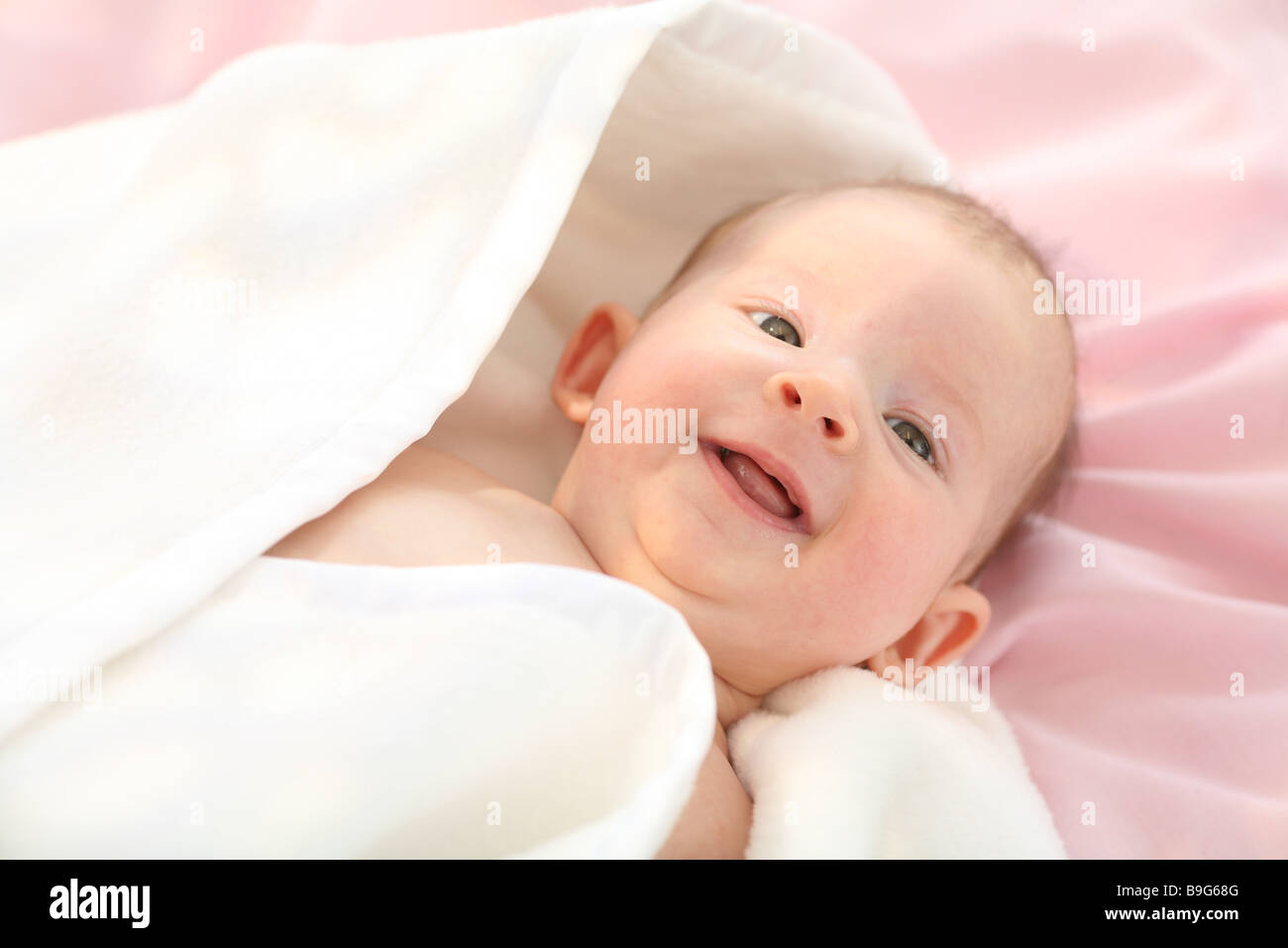 Baby lying supine position laughing blankets enveloped portrait 3 months resting observing baby gaze camera blankets - Stock Image