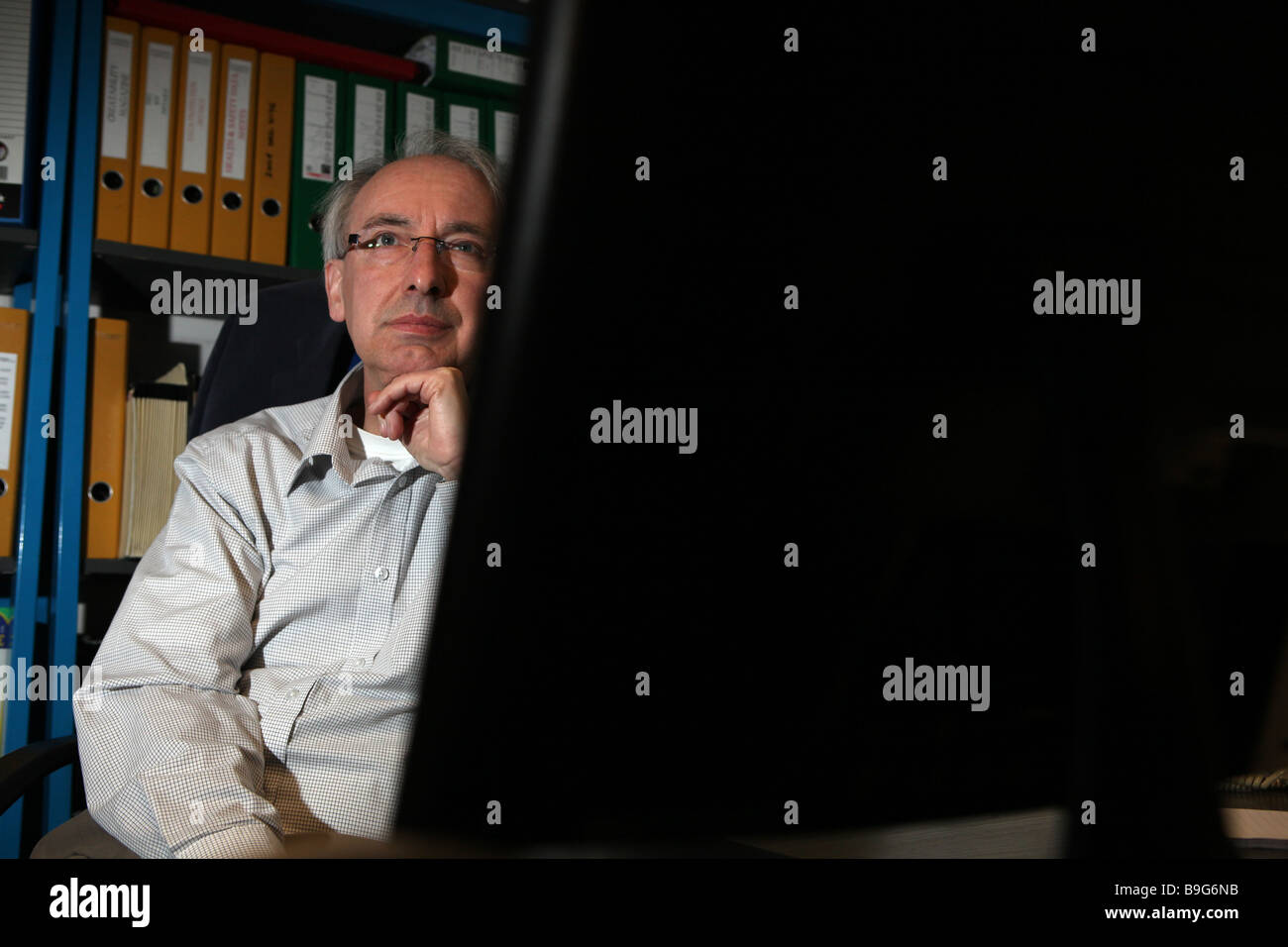 a portrait of a older man sitting in front of a computer looking very learned and thoughtful  there is a bookcase - Stock Image