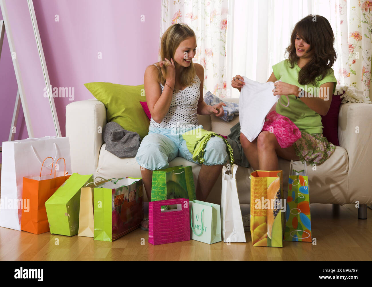 girl  sofa  purchase-bags  sit squeals  garments  views  cheerfully  series  people  teenagers  friends  two  friendship - Stock Image