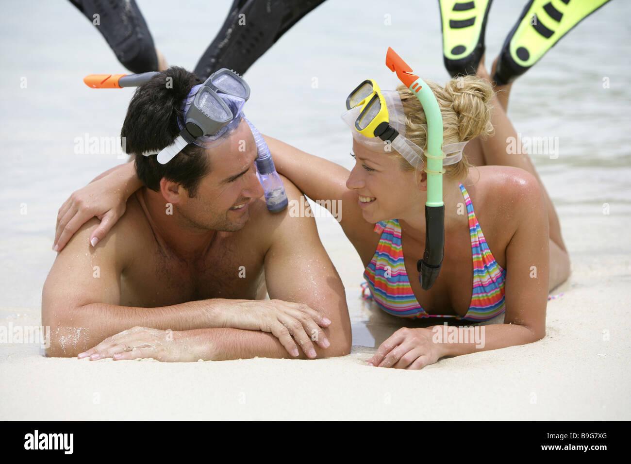 Liveliness bath-clothing bathing beach-holidays touch relationship gaze camera relaxation relaxation flirt fins - Stock Image