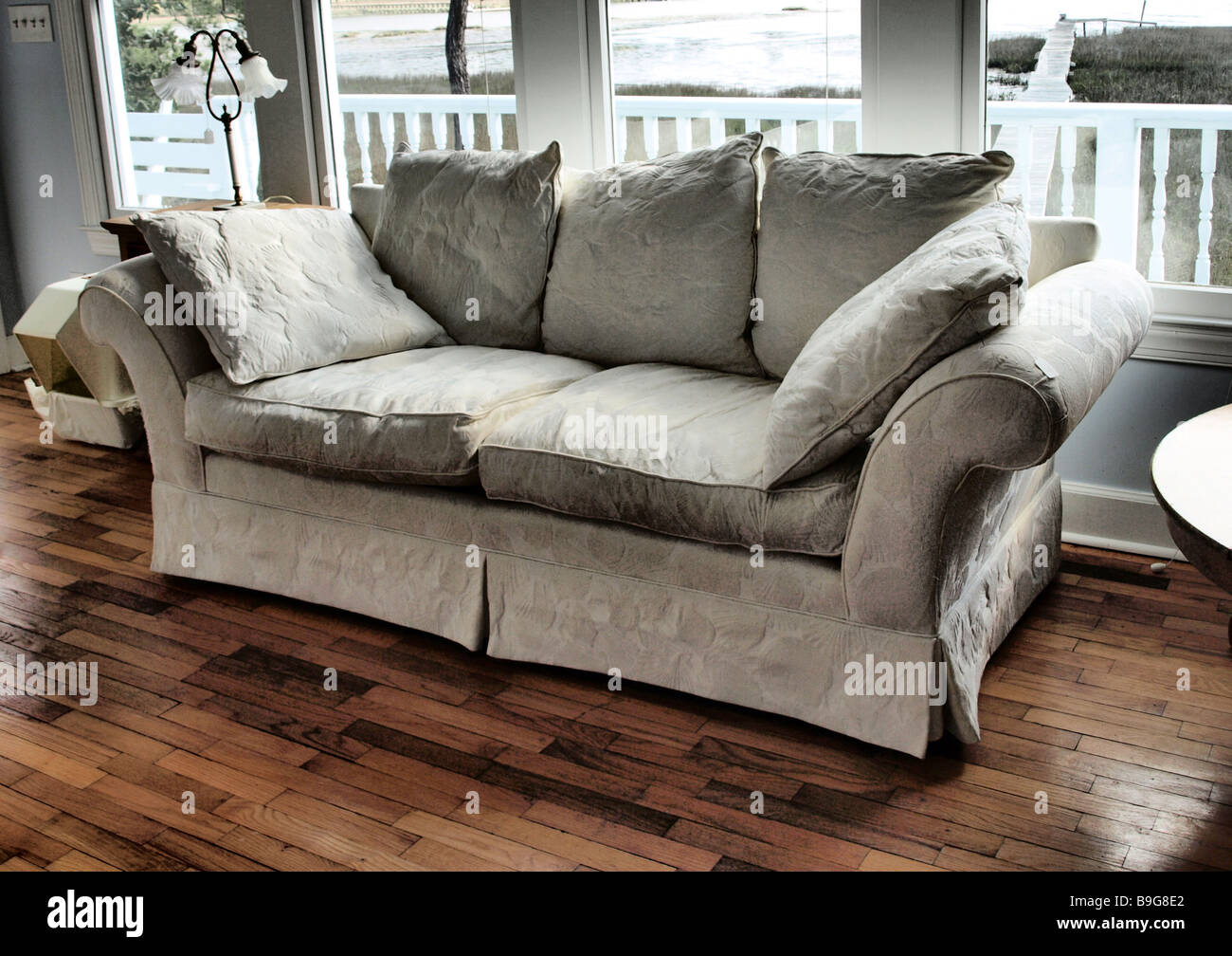 sofa couch on wooden floor with window in back looking to fence gray - Stock Image
