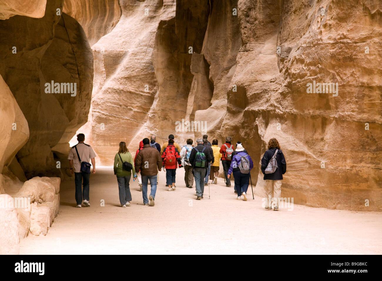 Tourists on a guided tour walk through the Siq on their way to Petra, Jordan - Stock Image