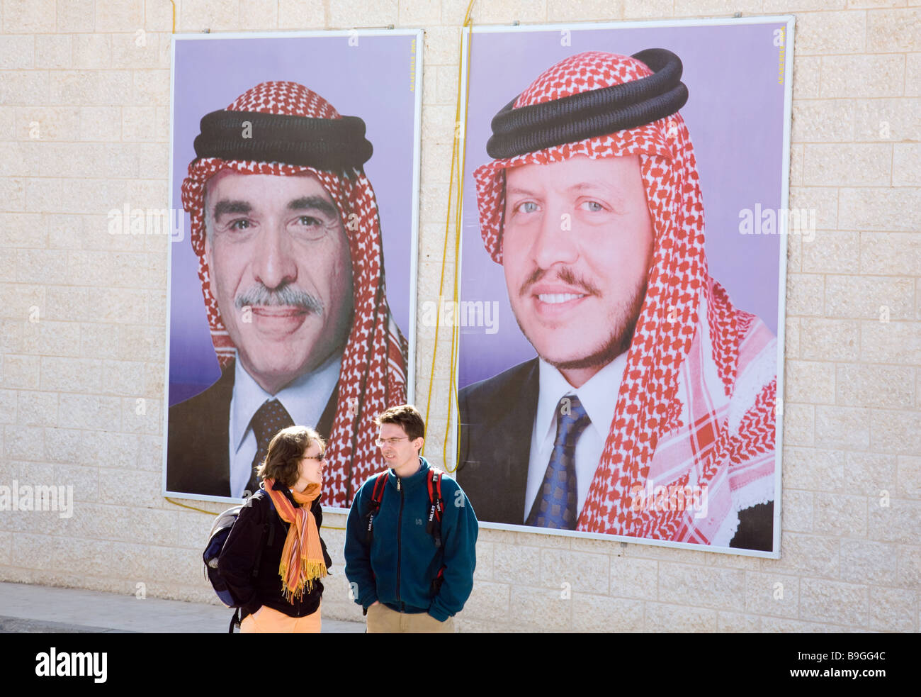 A tourist couple talk in front of posters of King Hussein and his son, King Abdullah of Jordan; jordan, Middle East - Stock Image