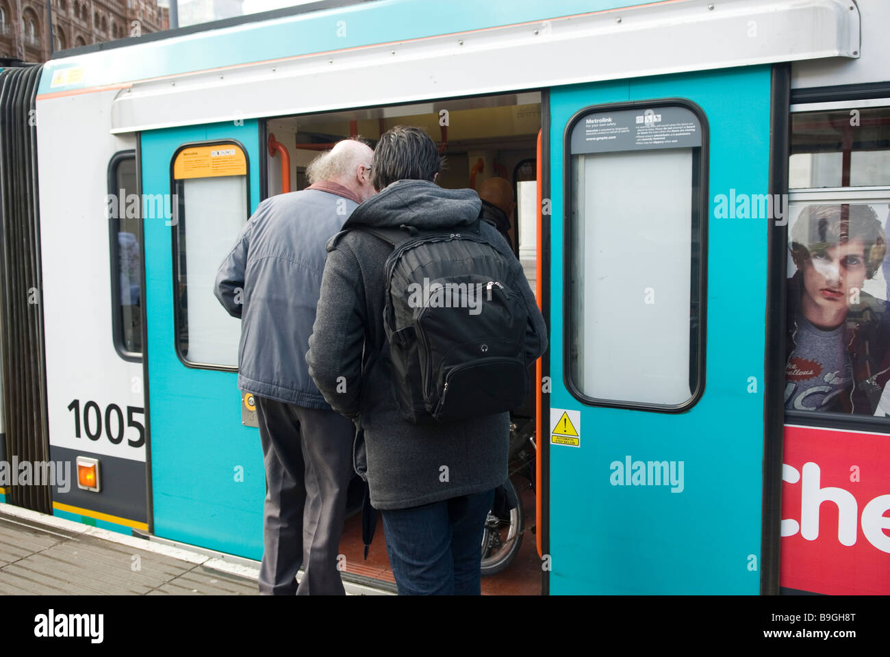 People getting on the Tram Manchester city centre UK - Stock Image