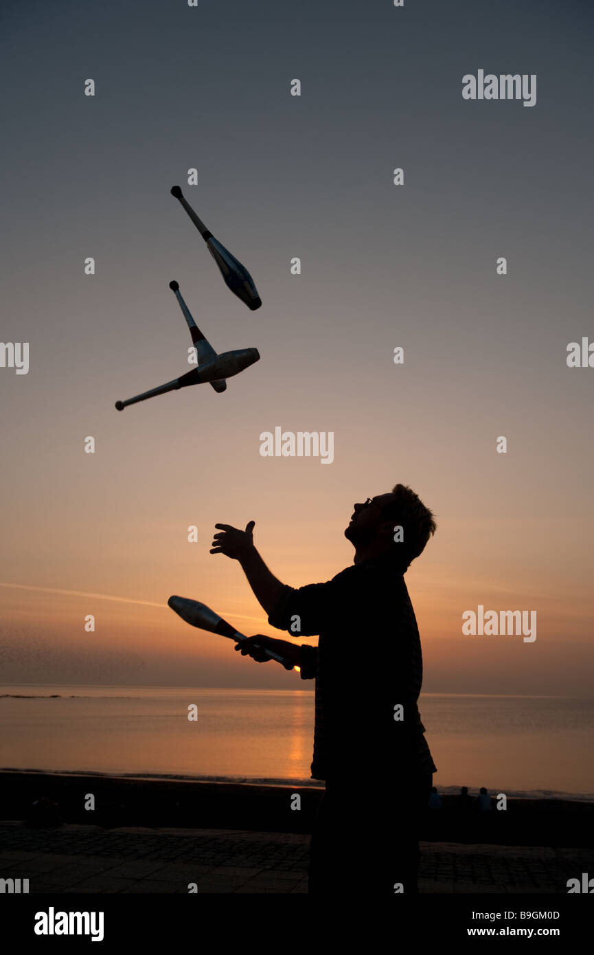 A man in silhouette practising juggling with 4 clubs at sunset on a beach by the sea ocean, Aberystwyth wales UK - Stock Image
