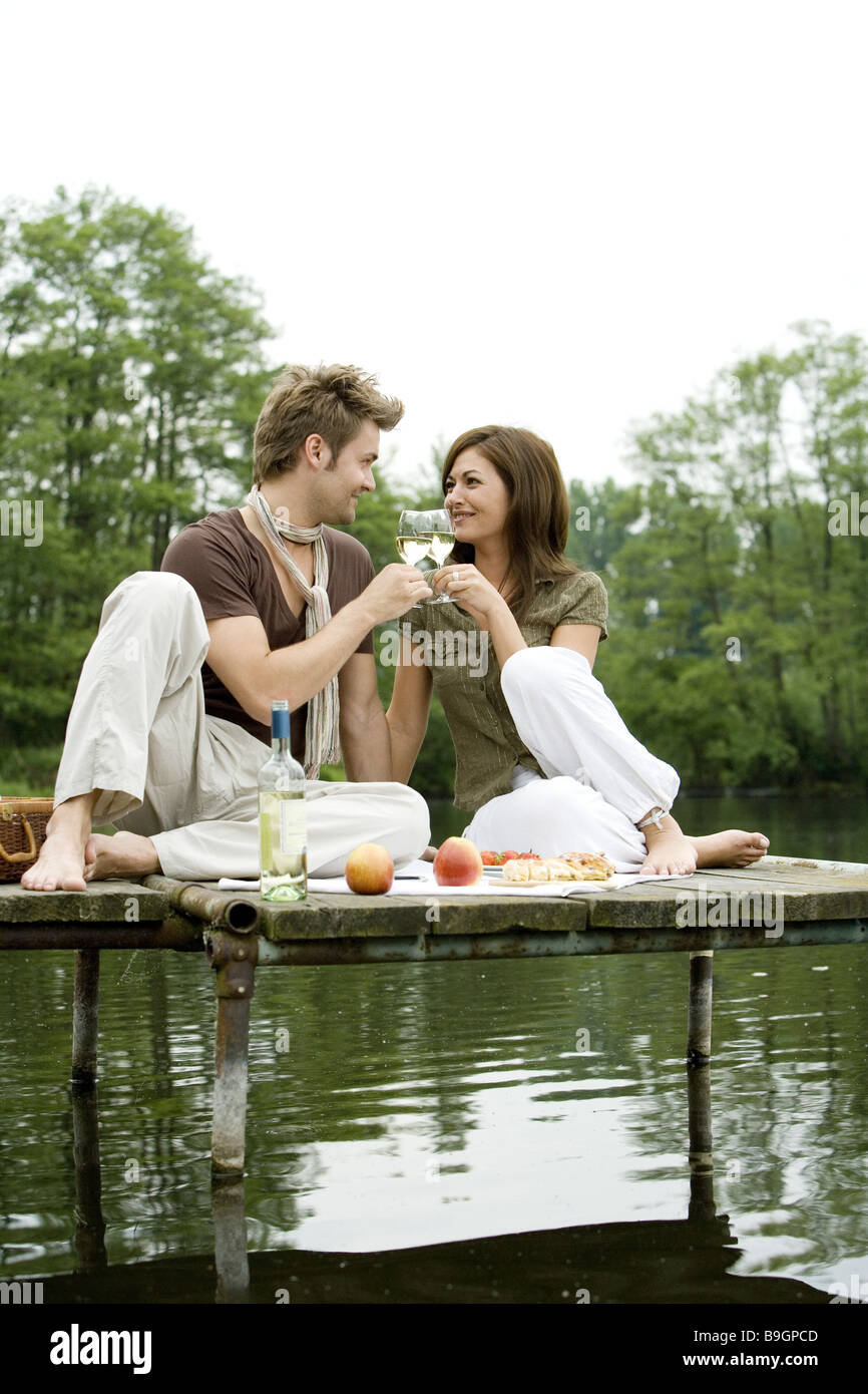 lake pair bridge fallen in love sitting picnic clink glasses resting bath-bridge gaze-contact snack relaxation leisure - Stock Image