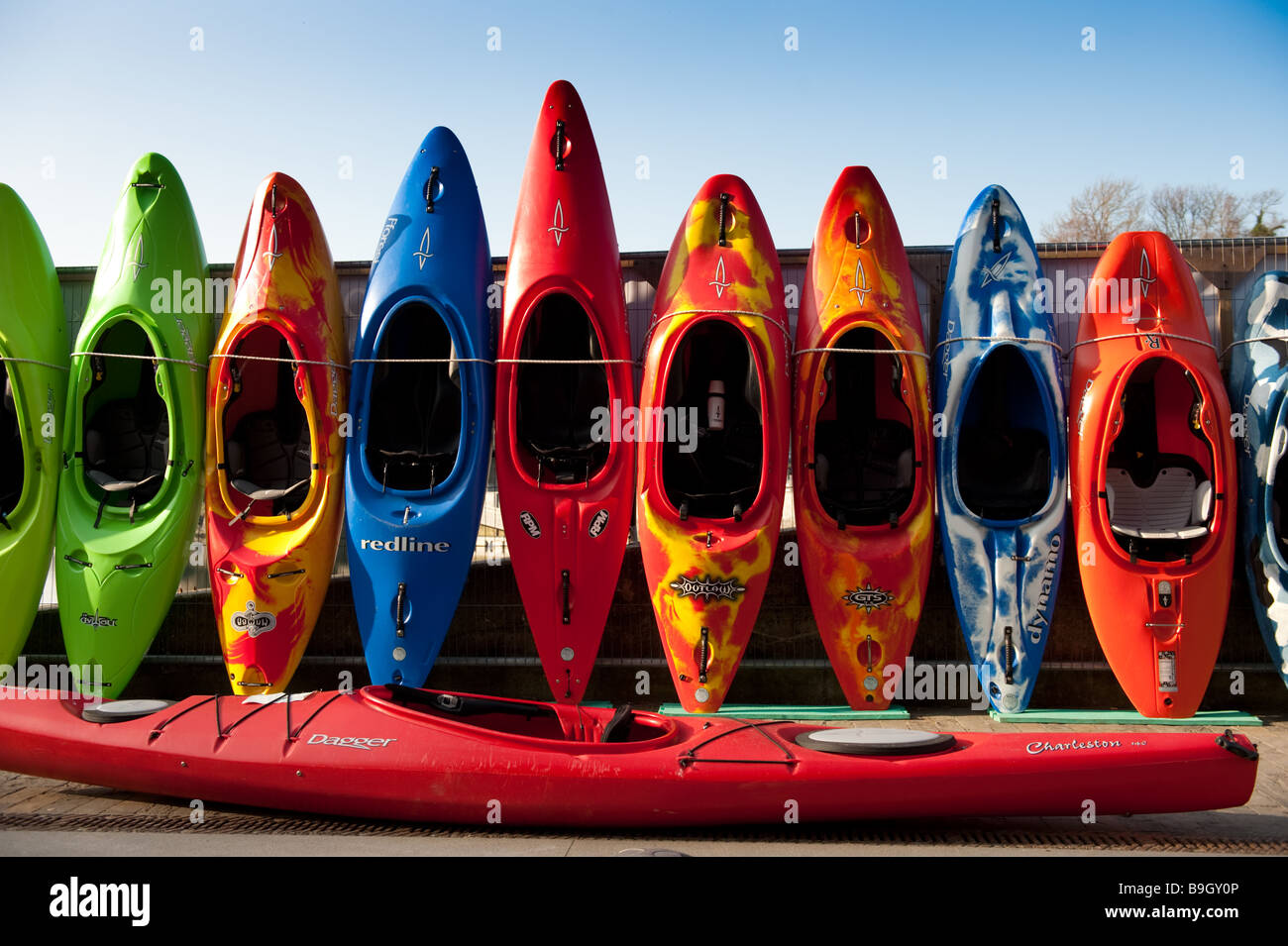 Row of colourful kayaks and canoes for sale Cardigan Town Ceredigion West Wales UK - Stock Image