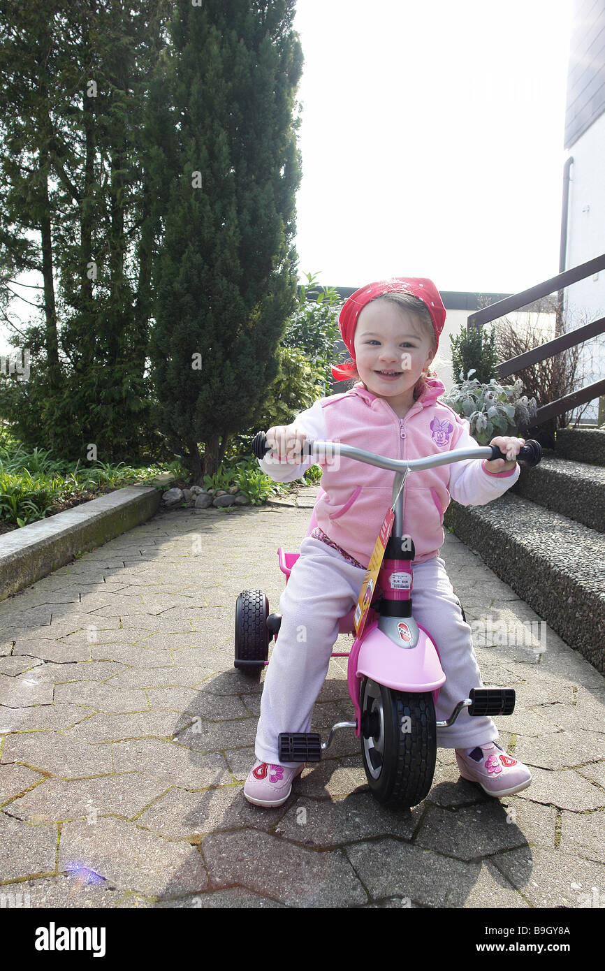 Toddler tricycle outside cheerfully laughs - Stock Image