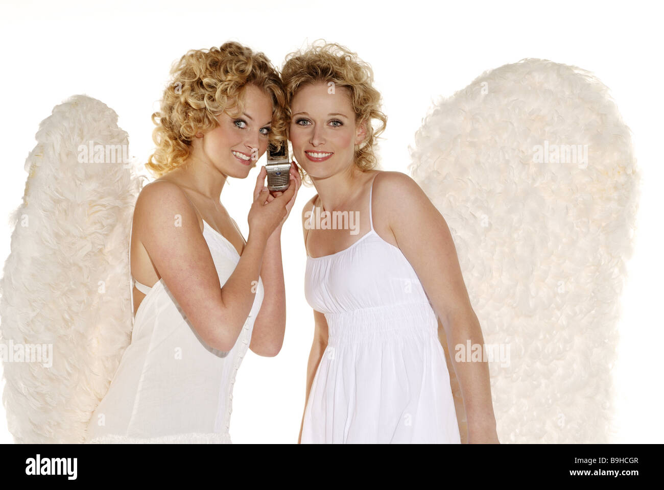 Women young blond angel wings smiling telephones cheerfully cell phone together semi-portrait christmas people christmas - Stock Image