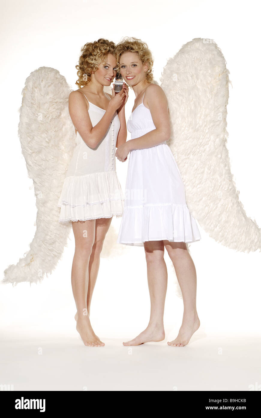 Women young blond angel wings smiling telephones cheerfully cell phone together barefoot christmas people christmas - Stock Image