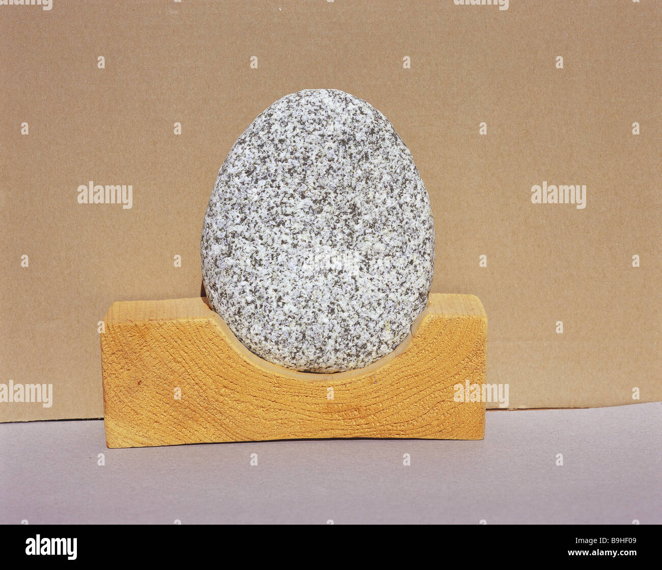 nature-art wood stone stone shingle river-shingle round oval gray scrutinized granite wooden-pedestal semicircle - Stock Image