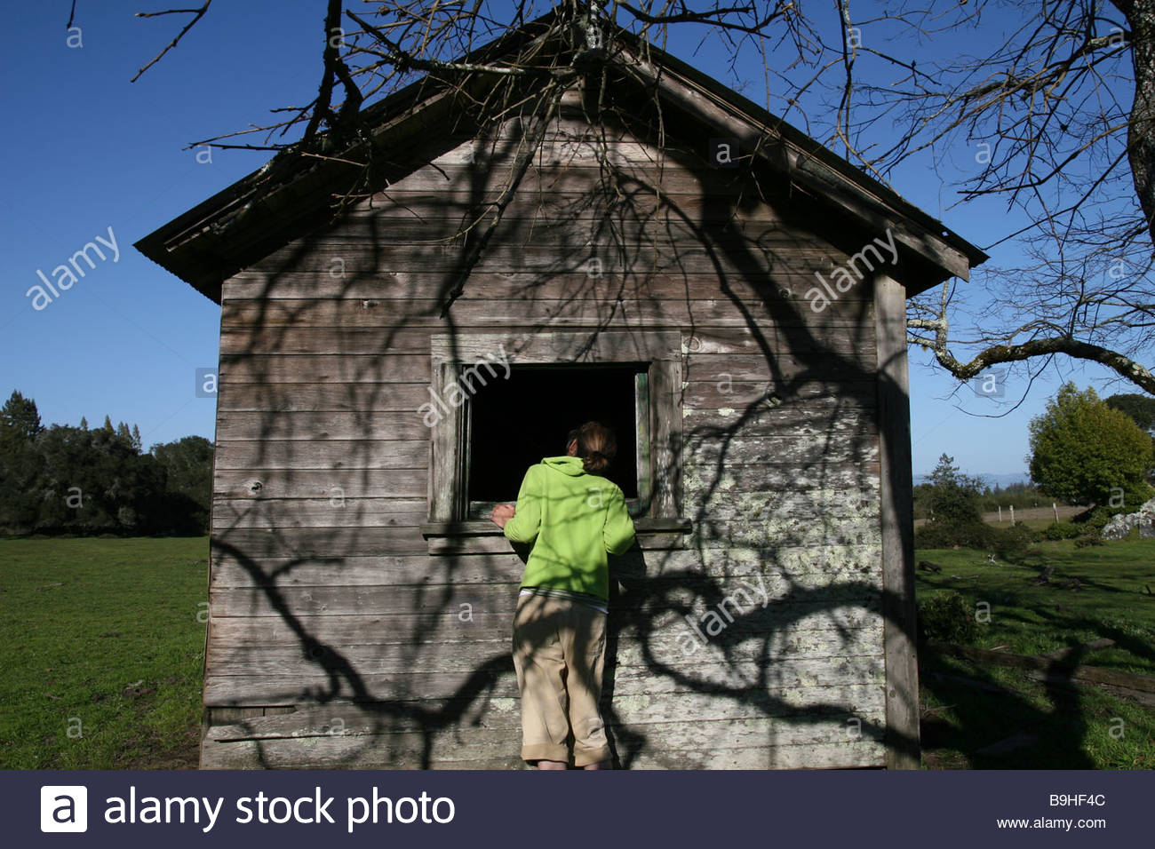 A woman looking into the window of a shack. - Stock Image
