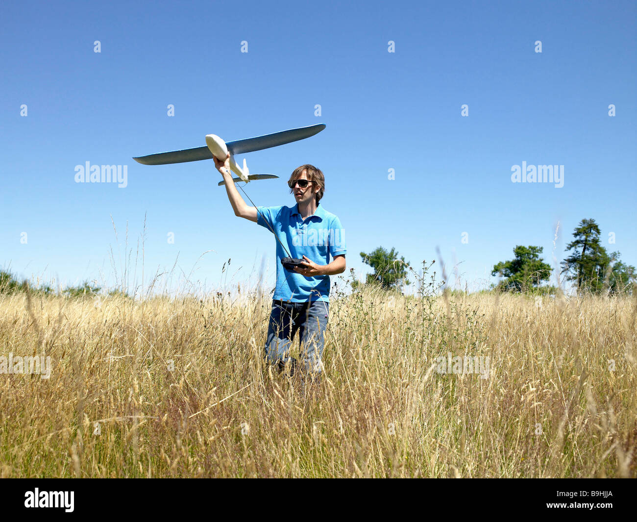Man playing with remote-controlled plane - Stock Image