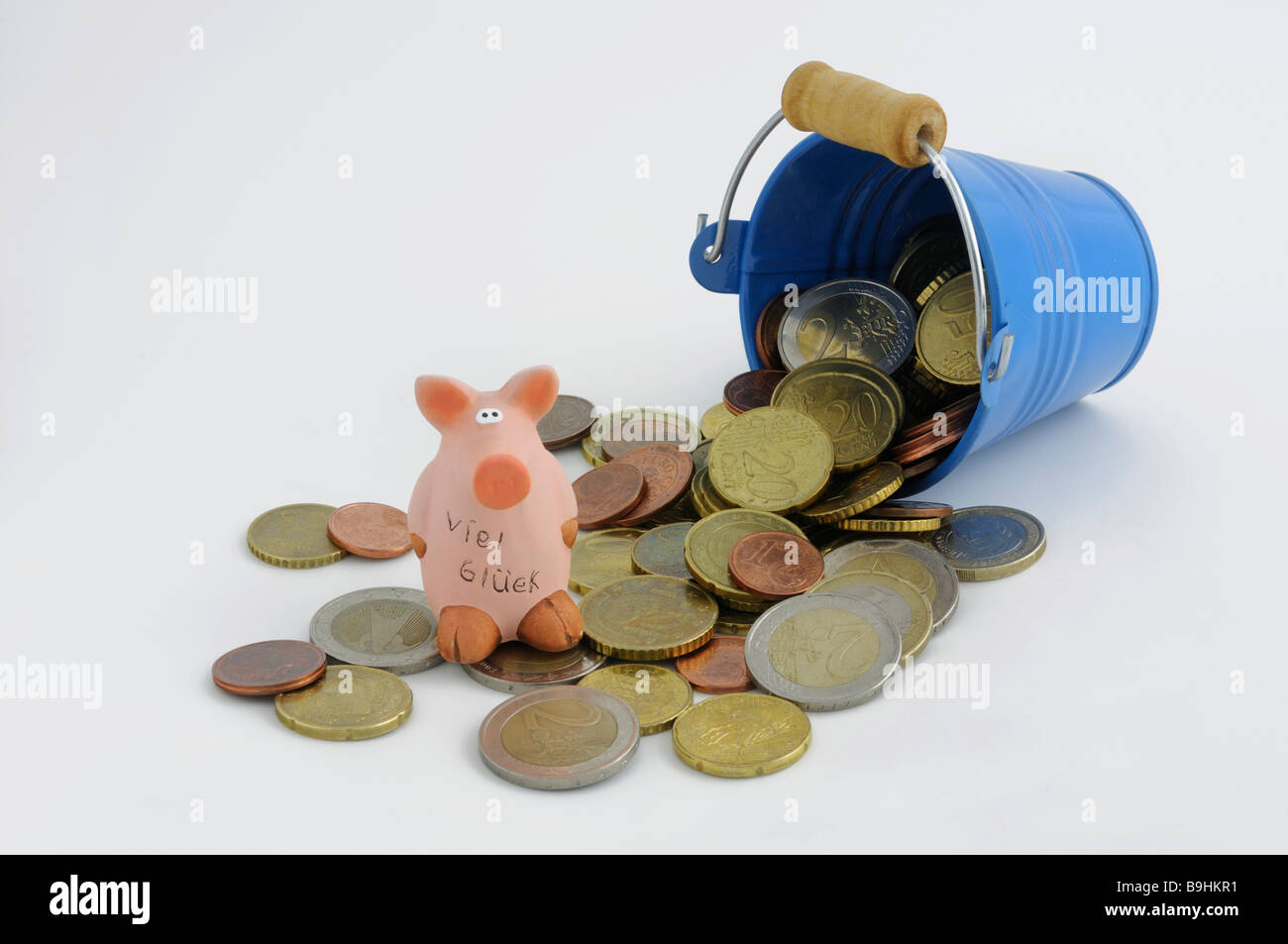 Tipped over bucket with euro coins and a lucky pig - Stock Image