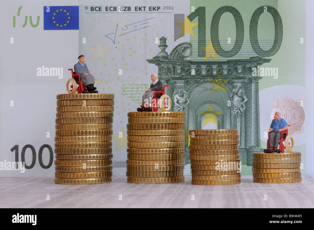 Figures of wheelchair users on stacks of coins, in front of a 100 eur bill, symbolic picture for attendance allowance - Stock Image