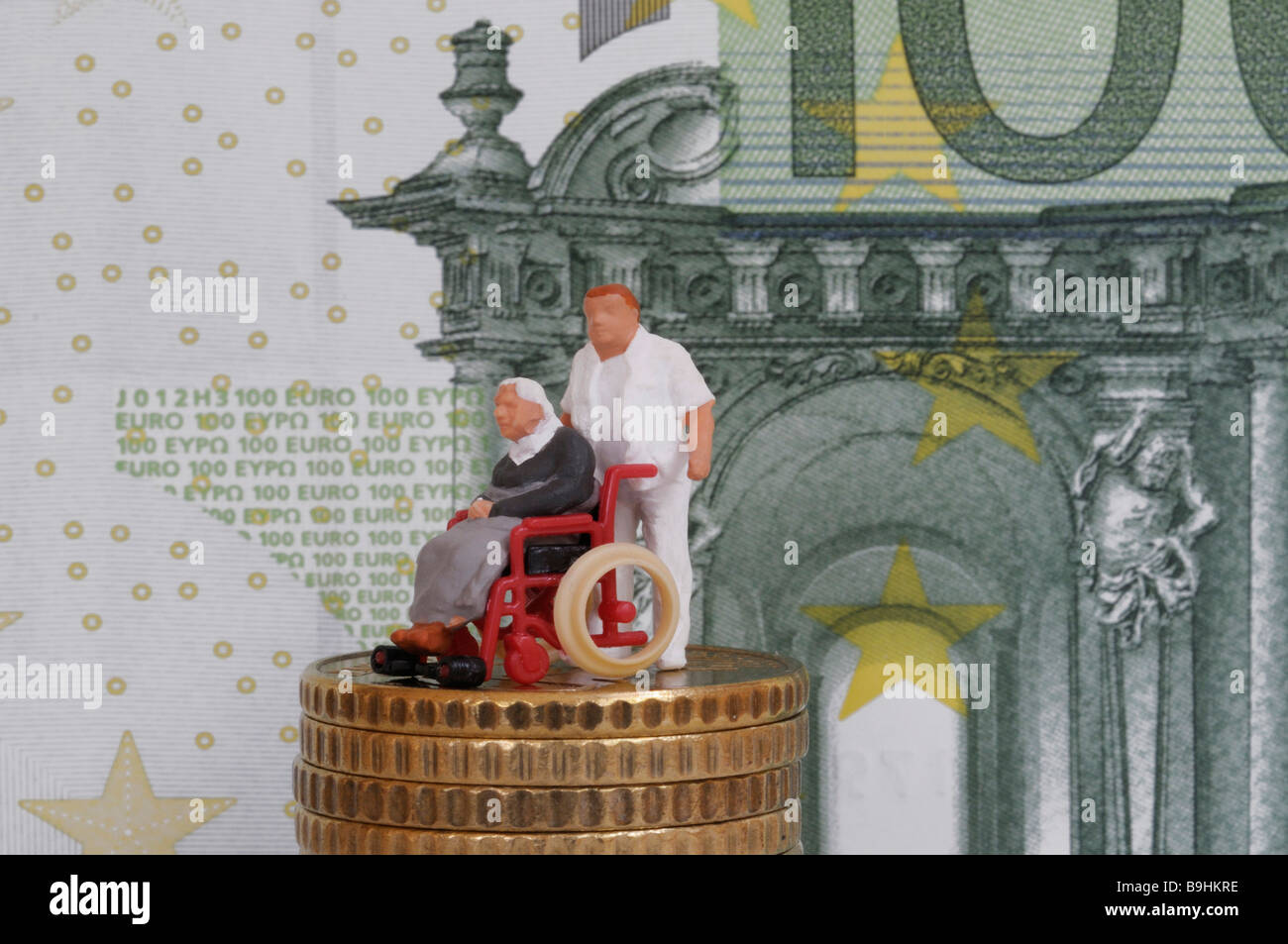 Male nurse pushing an old person in a wheelchair, figure on a stack of coins in front of a 100 eur bill, symbolic - Stock Image