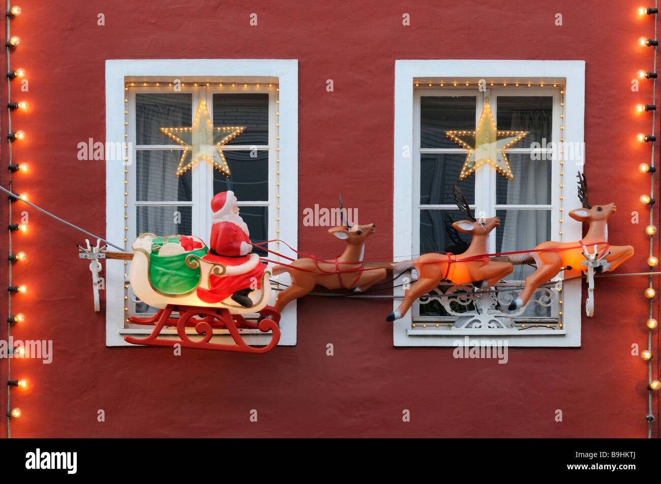 Christmas decoration, Santa on sleigh drawn by reindeer on a red house with white crown glass windows - Stock Image