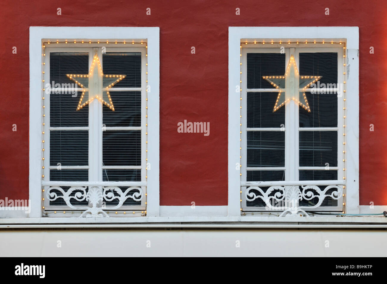 Christmas decoration, stars and chain of lights on crown glass windows - Stock Image