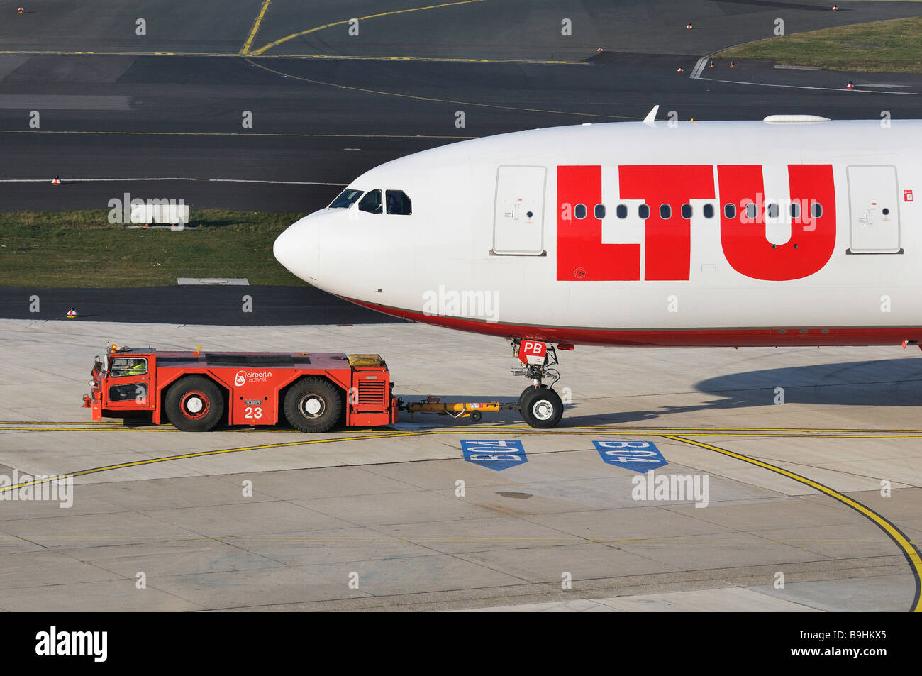 LTU commercial aircraft in the manoeuvring area with marshalling yard vehicle, Duesseldorf International Airport, - Stock Image